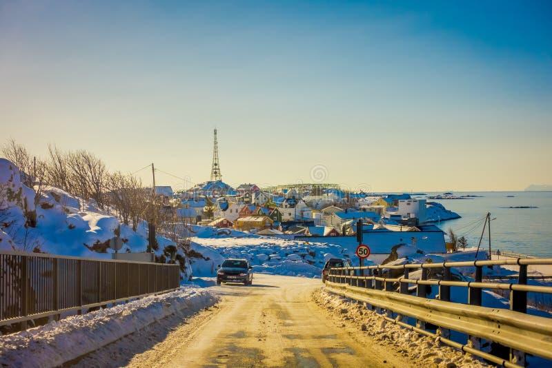 Henningsvaer,挪威- 2018年4月10日:用雪和汽车报道的冻街道室外看法在路有一些的 库存图片