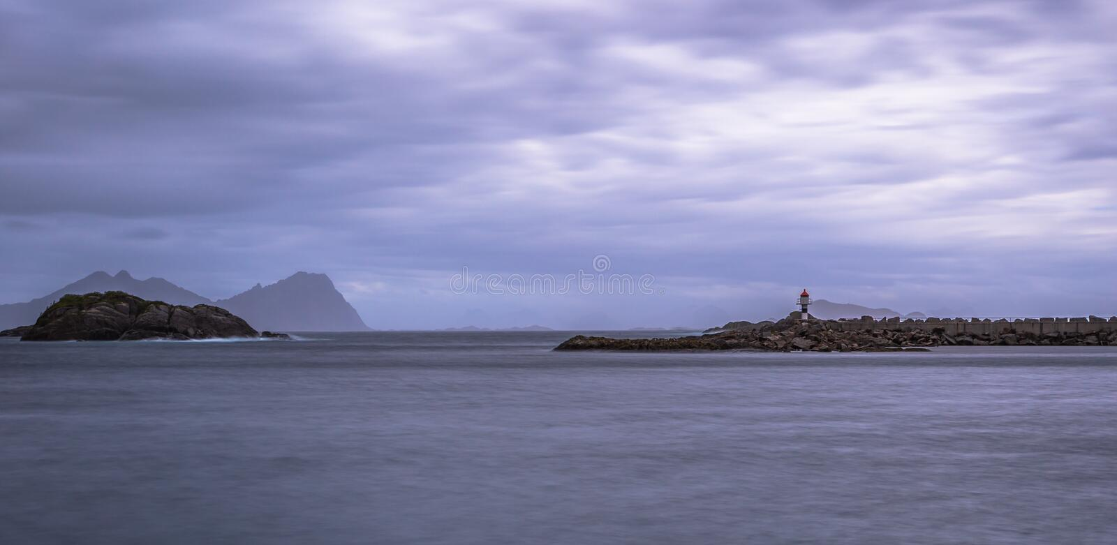 Henningsvaer- June 15, 2018: Distant lighthouse of a small village in the Lofoten Islands, Norway royalty free stock photography