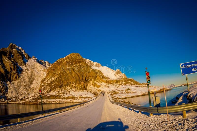 Henningsvaer Norge - April 04, 2018: Den utomhus- sikten av den djupfrysta gatan täckte med snö och trafikljus ett informativt royaltyfria foton