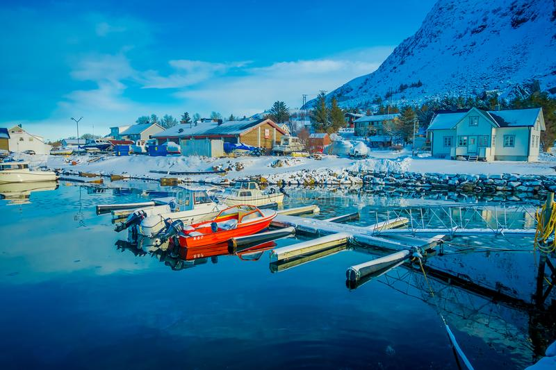 Henningsvaer, Norway - April 04, 2018: Outdoor view of small fishing boats in a fishing port with a mountain reflection stock photography