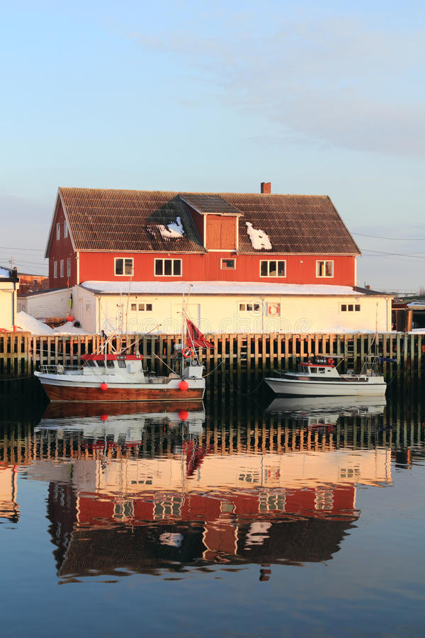 Henningsvaer red building and boats mirroring. Mirrors in Henningsvaer's main channel, Lofoten islands, Norvegian arctic sea royalty free stock image