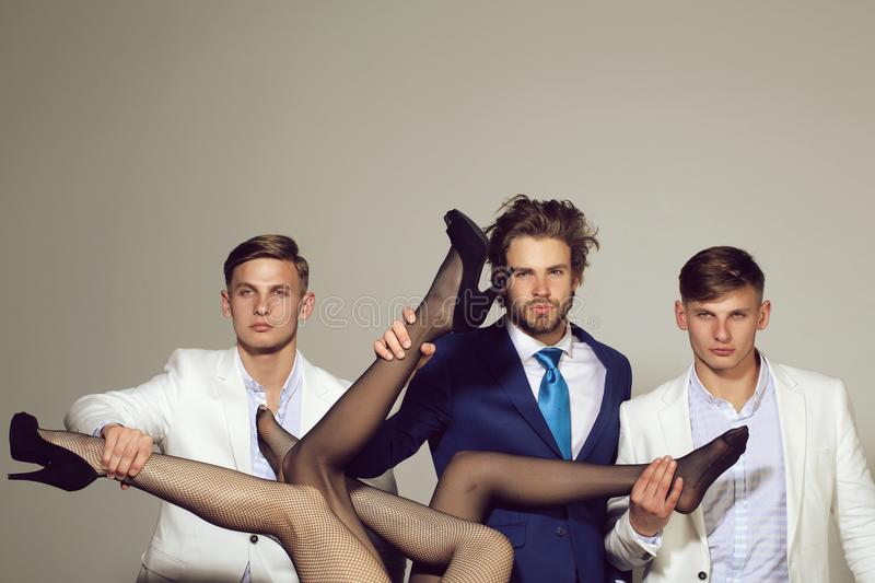 Henpecked. fashion and business, men holding female legs, luxury and patriarchy. Henpecked. fashion and business, handsome men in suit holding female legs in stock photography