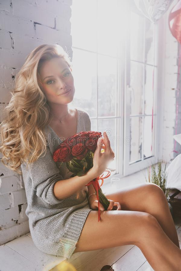 Her beauty shines through. Attractive young woman holding a bouquet and smiling while sitting on the floor in the bedroom royalty free stock photo