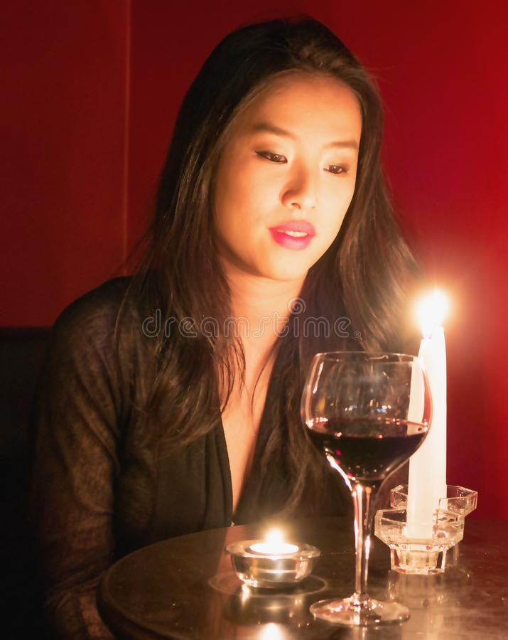 With a face glowing in candle light a lovely lady sits at a table. With her face glowing in candle light a beautiful Asian woman gazes at candles as a glass of royalty free stock image