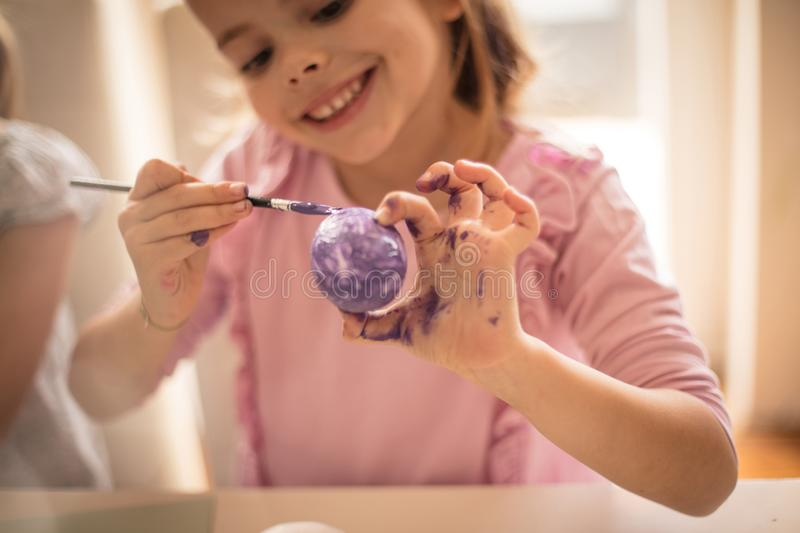 On her face you see happiness, the joy of the Easter. Little girls coloring Easter egg royalty free stock images
