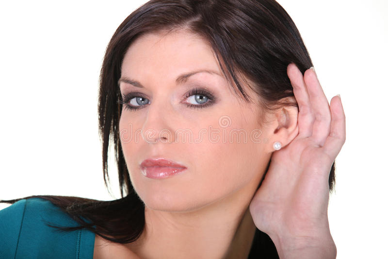 Her hand to her ear. Woman with her hand to her ear royalty free stock photo