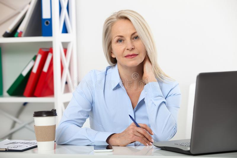 Her job is her life. Business woman working in office with documents. Beautiful middle aged woman looking at camera with stock photo