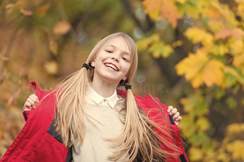 In her own style. Kid girl wear coat for autumn season nature background. Child cheerful on fall walk. Warm coat best. Choice for autumn. Keep body warm clothes stock image