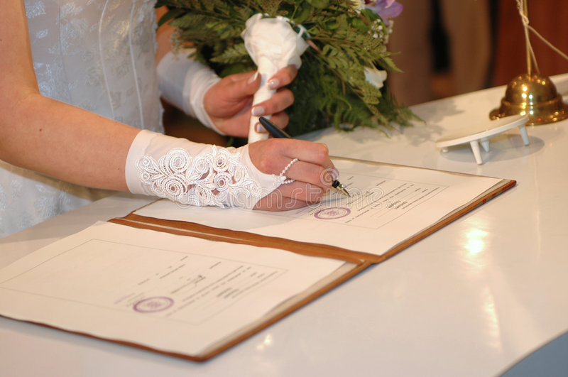 Her signing it (Wedding ceremony) stock photos