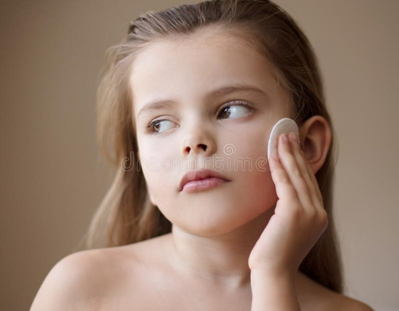 Her skin like a silk. Little girl cleaning her face. Close up royalty free stock image
