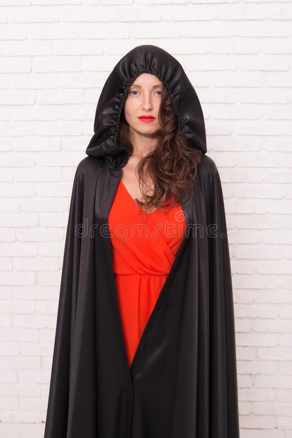 Her sorcery skills are just far too impressive. Halloween party girl. Sexy girl wearing hooded black cloak on white. Brickwall. Mysterious girl with classic royalty free stock photo