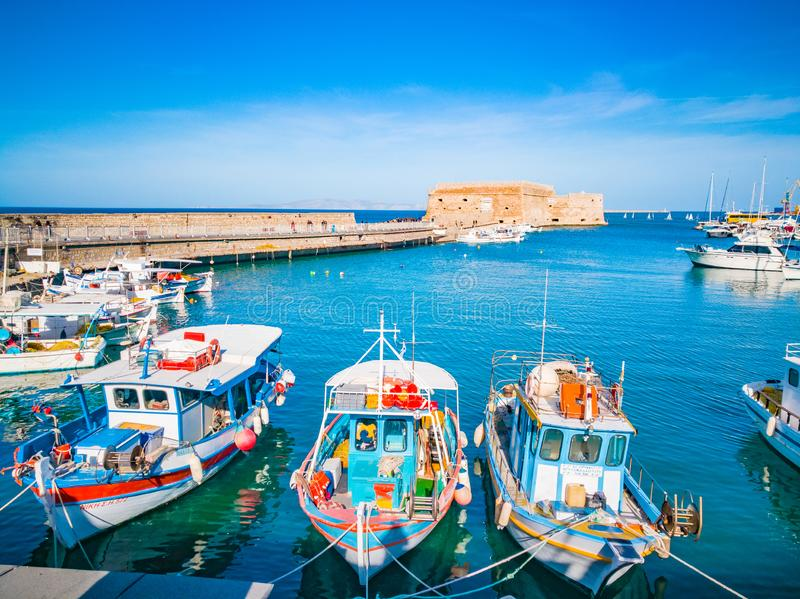 Heraklion, Crete beautiful view to harbor. Heraklion Koule, fortress. Blue sky and turquoise sea at the port of Heraklion city. Co. Lorful boats in Greek port royalty free stock images