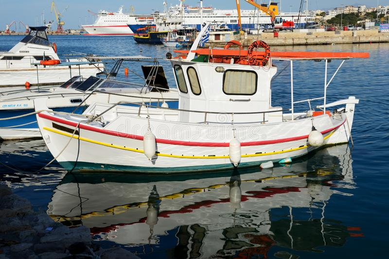 The traditional Greek fishing boat are near pier and tourists stock photos