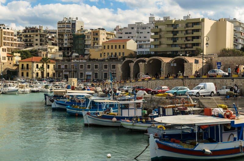 HERAKLION GREKLAND - November, 2017: färgrika fiskebåtar near den gamla Venetian fästningen, Heraklion port, Kreta arkivfoto