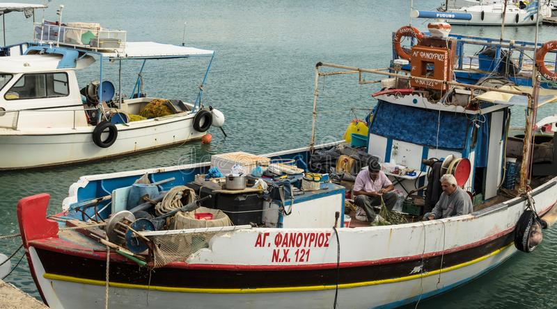 HERAKLION GREKLAND - November, 2017: Grekiska fiskare, som demontera fisknät, Venetian fästning, Heraklion port, Kreta royaltyfri foto
