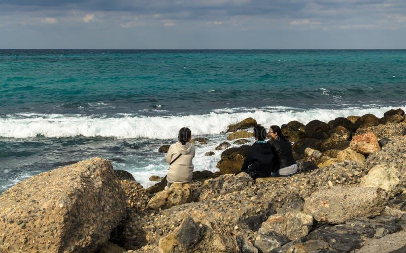 HERAKLION GREKLAND - November, 2017: Turister som vilar på stenarna vid havet nära den gamla Venetian fästningen, Heraklion port, royaltyfri fotografi