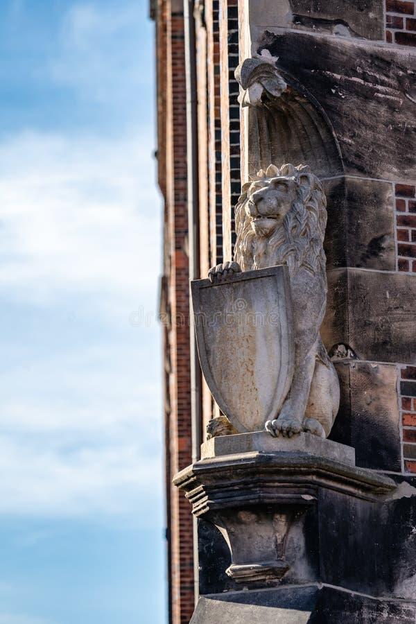 Heraldic lion statue with shield. Heraldic stone carved lion statue with shield on a plinth on the corner of a historic brick building stock photography