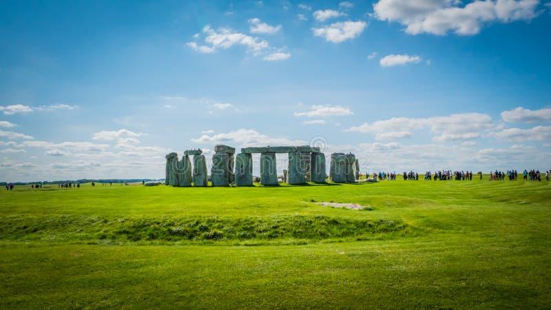 Herança do UNESCO de Stonehenge perto de Salisbúria, BRITÂNICO com uma linha de visitantes imagem de stock