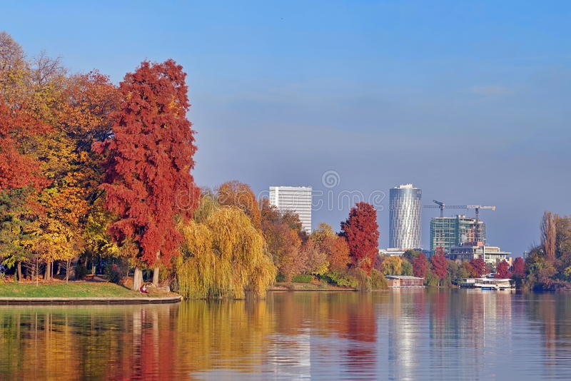 Autumn landscape in the Herastrau park. Colored trees and Floreasca City Center in background - landmark in Bucharest, Romania royalty free stock image