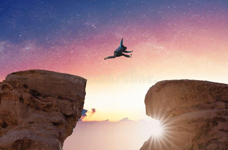 Herausforderungs-, Risiko-, Freiheits- und Fantasiekonzept Silhouettieren Sie einen Mann, der über Abgrundüberfahrtklippe springt stockfoto