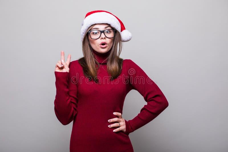 Herausgenommenes Weihnachtsmädchen mit dem Sankt-Hutfinger oben stockfotos