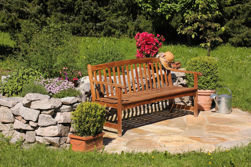 Herb garden, watering can and bench. Garden with bench, herbs and box tree stock photos