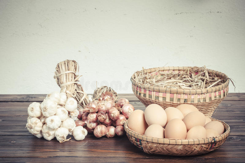 Herb ingredients, onion, garlic and eggs on dark wood table. With speckled background, retro style stock photos