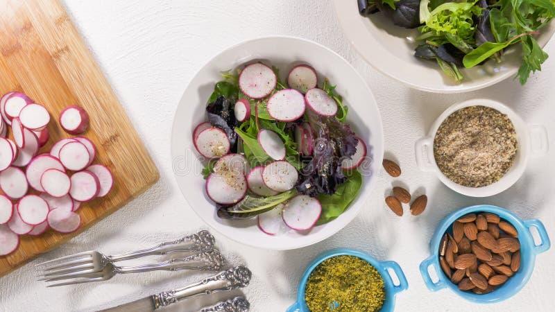Herb Mix Salad con il ravanello organico fresco, le lattughe, gli spinaci, un certo olio vegetale del condimento, del mandorla e  immagine stock