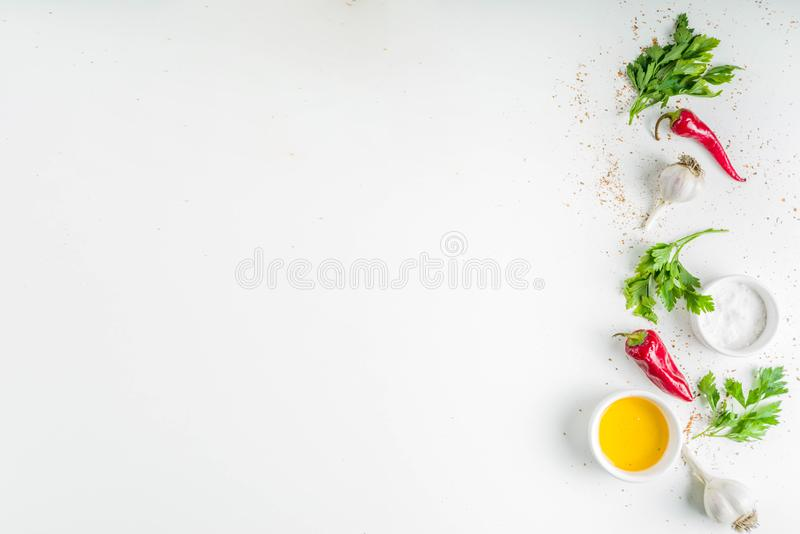 Herb and spices cooking background. Olive oil, salt, garlic, parsley, hot red peppers chili, for cooking  homemade dinner. On a white background, copy space royalty free stock photography