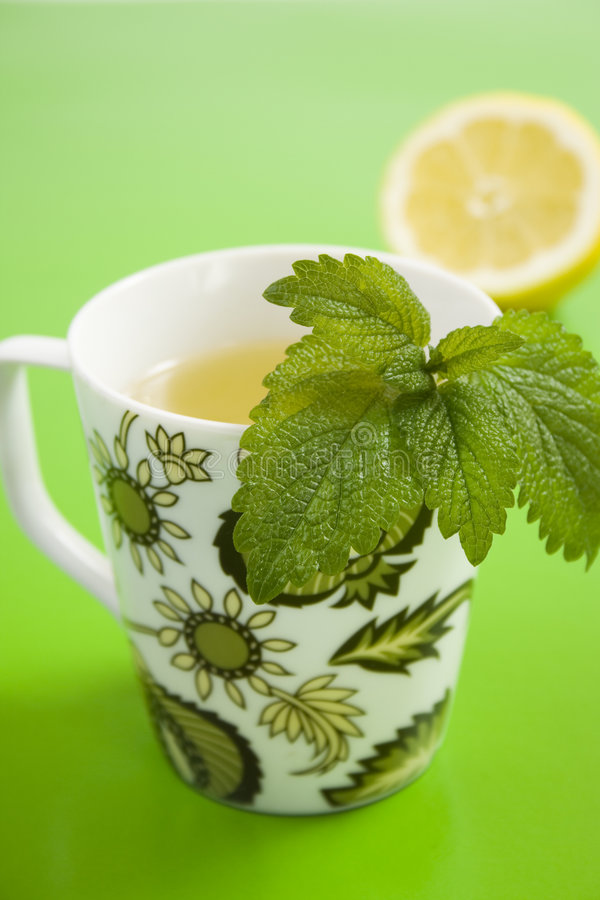 Herb tea with lemon and lemongrass. On green table royalty free stock photography