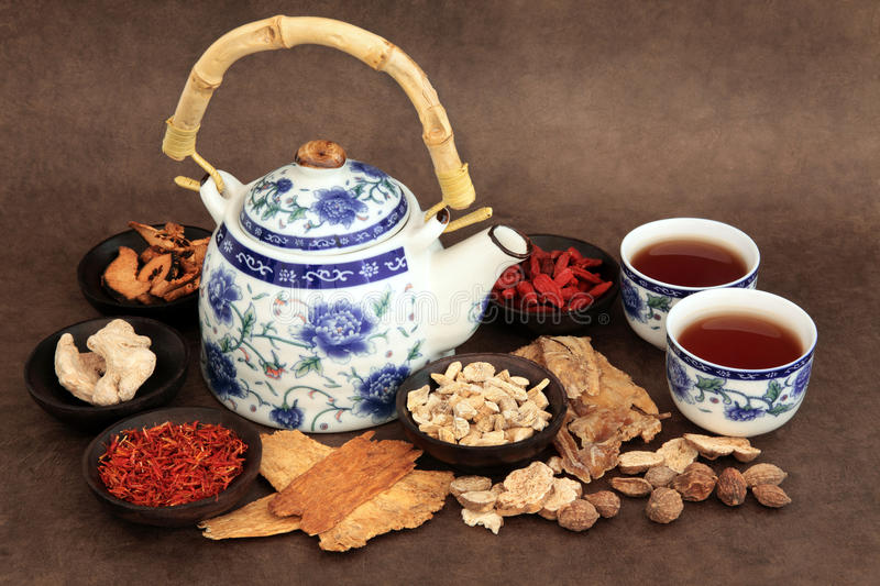 Herb Tea Selection. Chinese herb tea selection with traditional teapot and cups over brown lokta handmade paper background royalty free stock photos