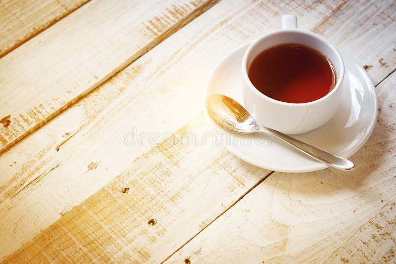 Herbaciana filiżanka i łyżka na spodeczku z stołem ranku światło słoneczne dla kopii przestrzeni obrazy stock