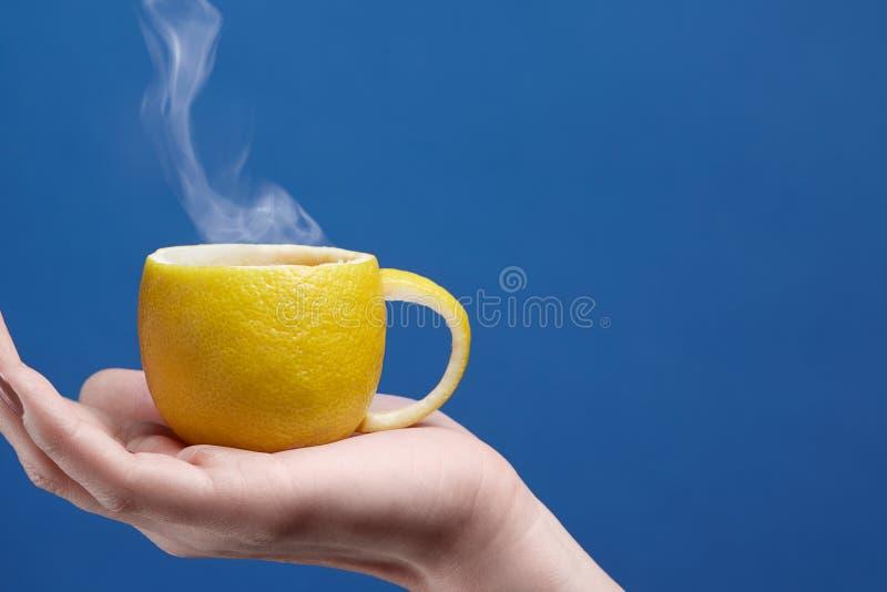 Herbaciana filiżanka robić cytryna Cytryny filiżanka w ręce na błękitnym tle Kreatywnie skład na temacie naturalna owocowa herbat fotografia stock