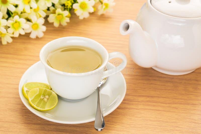 Herbaciana filiżanka z cytryną i garnkiem na stole obraz royalty free