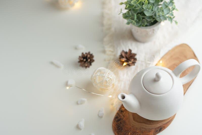 Herbaciany czas i herbaciany pić, Biały porcelany teapot z akcesoriami na drewnianej desce na białym stole na widok kopia zdjęcia stock