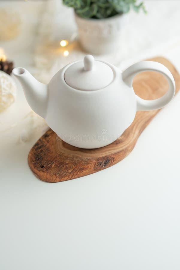 Herbaciany czas i herbaciany pić, Biały porcelany teapot z akcesoriami na drewnianej desce na białym stole na widok kopia obrazy royalty free