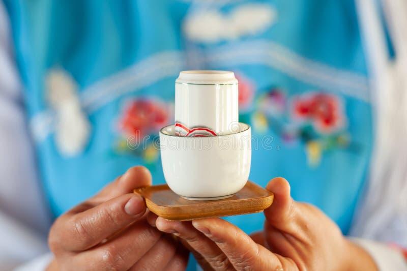 Herbaciany czas, piękna porcelany filiżanka herbata w yunnanese dziewczyn rękach przy herbata sklepem, Mae Salong wioska, Chiang  fotografia stock
