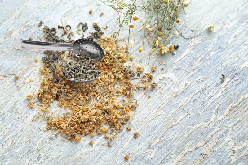 Herbaciany durszlak z wysuszonym chamomile kwitnie na drewnianym stole zdjęcie stock