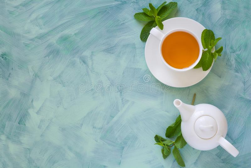 Herbaciany pojęcie Teapot i filiżanka z zieloną ziołową herbatą dekorowaliśmy nowych liście zdjęcia stock