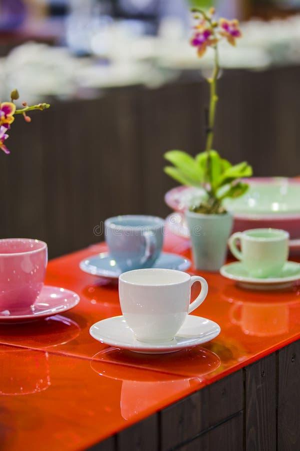 Herbaciany set, porcelany różni kolory kubki, dekorował stół dla herbaciany pić zdjęcie royalty free