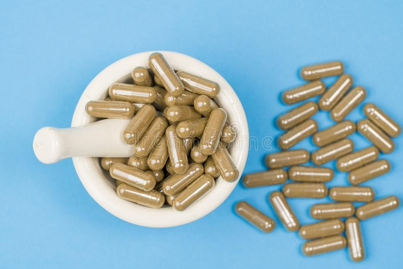 Herbal capsule and mortar on bluee background stock photography