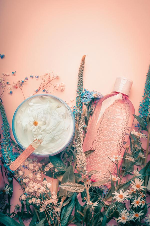 Herbal dermatology cosmetic cream and lotion with flowers . Skincare products on pastel background royalty free stock photo