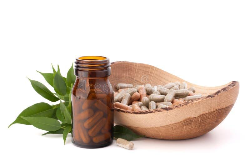 Herbal drug capsules in brown glass bottle. Alternative medicine royalty free stock images