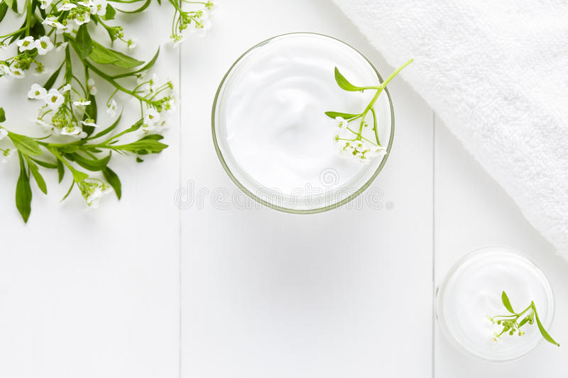 Herbal face cosmetic cream with flowers hygienic skincare product. Wellness and relaxation medical mask in glass jar on white background stock image