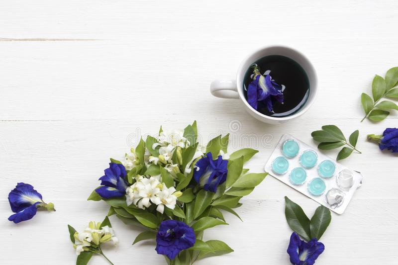 Herbal healthy drinks blue water extract butterfly pea flowers and lozenge cough sore pills. For health care with flowers arrangement flat lay style on stock photo