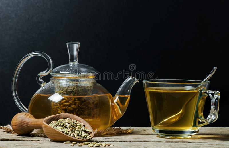 Herbal infusion fennel tea in glass cup with dried fennel seeds in wooden shovel stock images