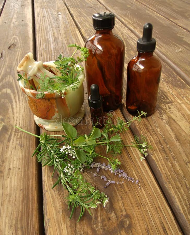 Herbal Medicine. Mortar, pestle, bottles, herbs, and medicine on a wooden slat background showing depth represents the making of herbal medicine stock photo