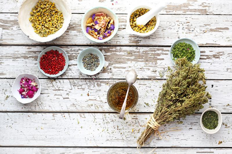 Herbal medicine and natural medicine. Traditional herbal remedies. A composition of herbs, flowers and spices. Healthful potions and infusions on a wooden table stock image