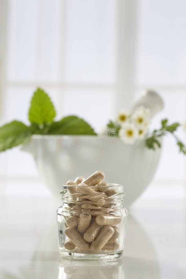 Herbal medicine pills and mortar over bright background royalty free stock image
