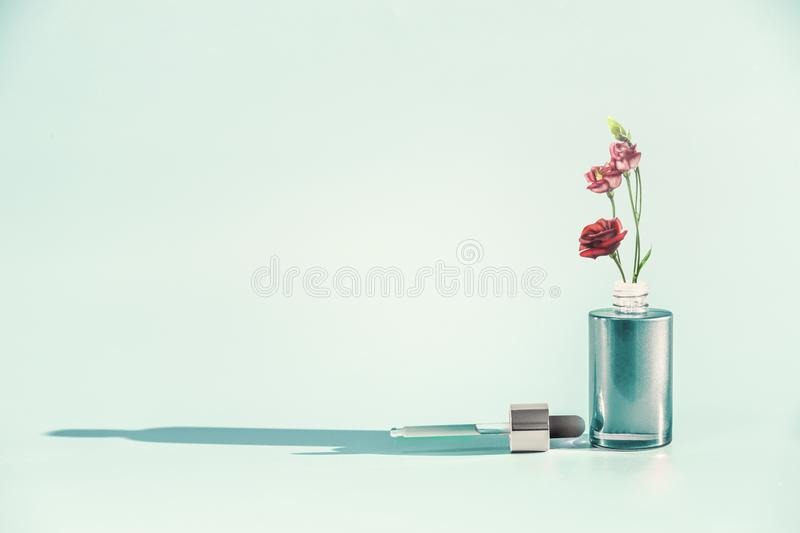 Herbal skin care cosmetics and beauty concept. Facial Serum or Oil bottle with dropper or pipette and flowers. Stand at blue background, front view. Modern stock photos